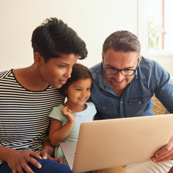 Cropped shot of a family of three using a laptop while sitting on their living room sofa